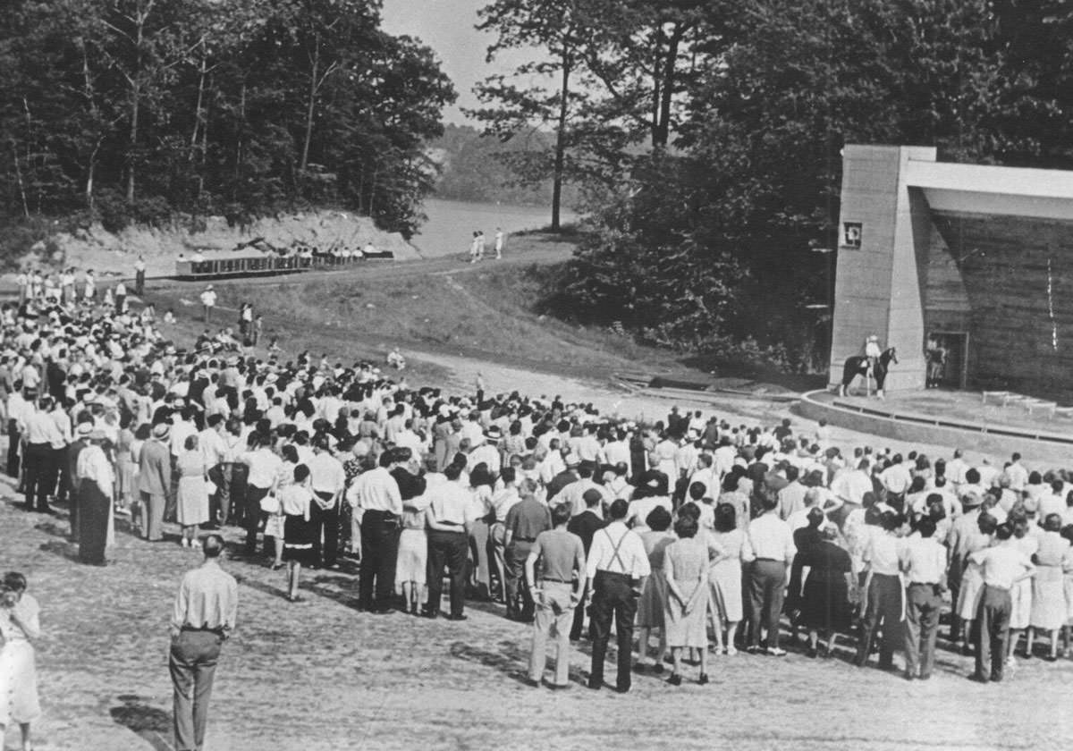 Black and white photo of visitors gathering and watching a man on a horse at an amphitheater at Seabreeze in 1940.