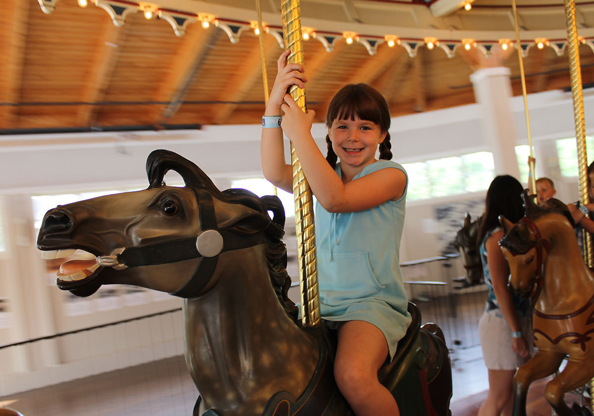Girl smiling and riding a horse on the carousel.