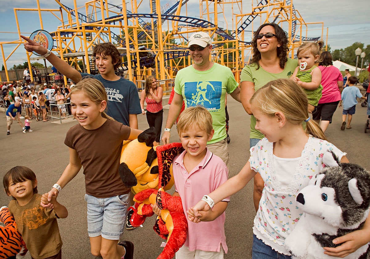 Family holding stuffed animal prizes and walking around the amusement park.