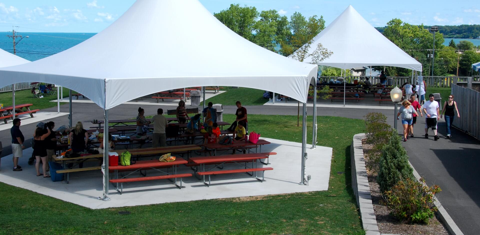 White Picnic Grove tents set up with picnic tables at Seabreeze.