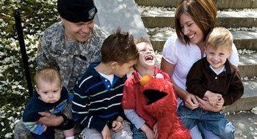 Military family sitting and laughing.