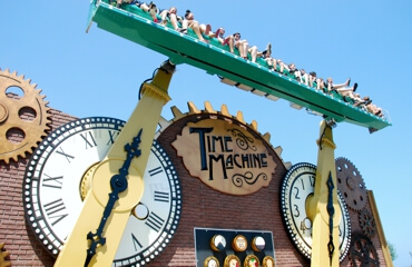 The giant clocks hands of the Time Machine thrill ride lifts riders in the air.