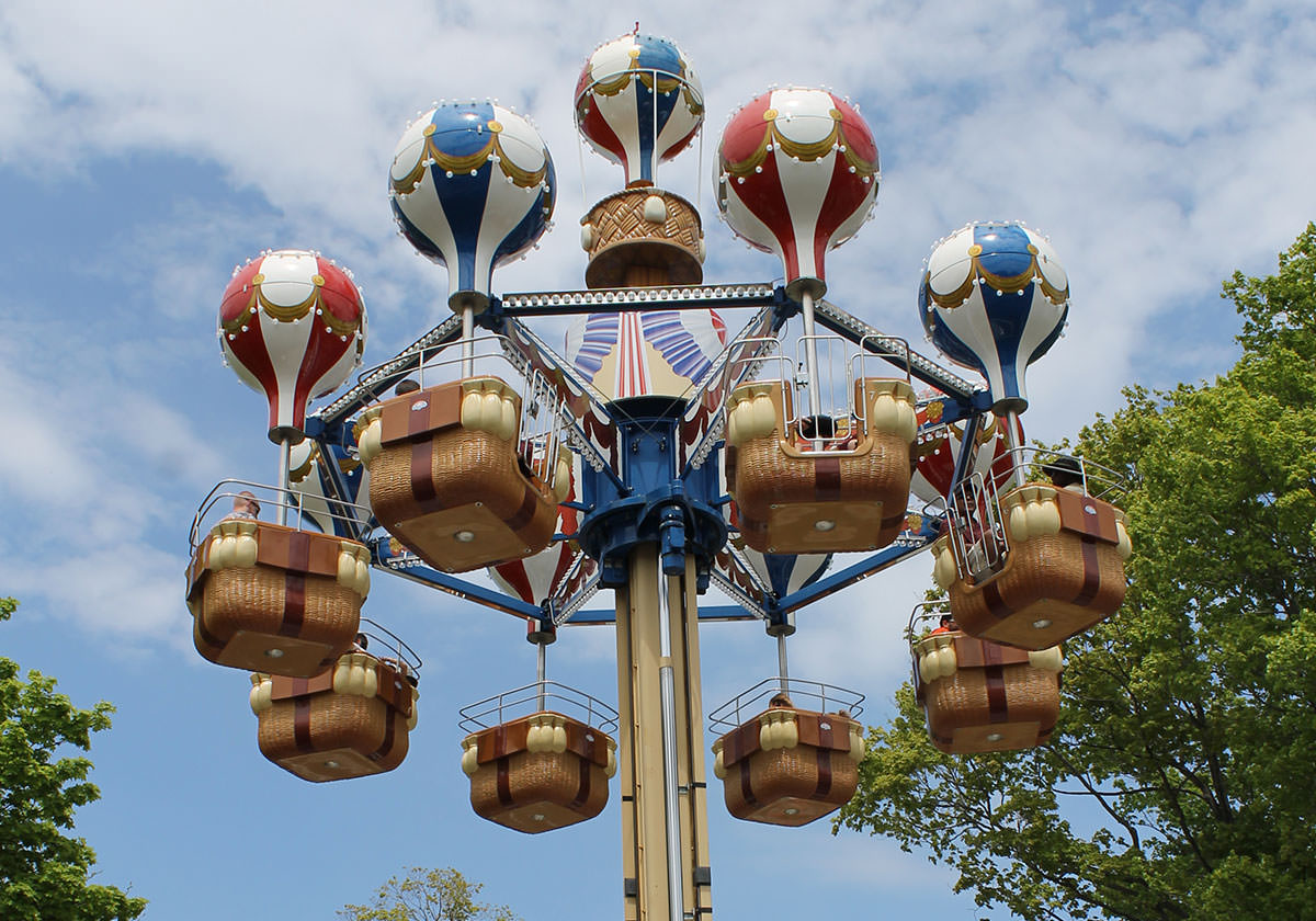 Ride with hot air balloons and riders in baskets shown in front of skyline.