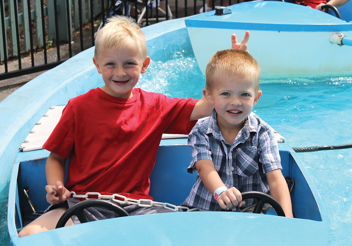 Two boys ride the kiddie boat ride at Seabreeze and smile.