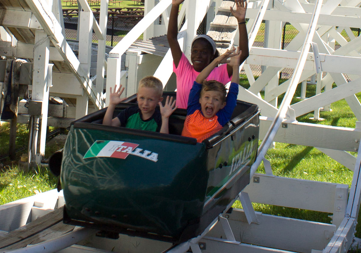 Children wave hands in the air while riding the Bob Sled rollercoaster ride.