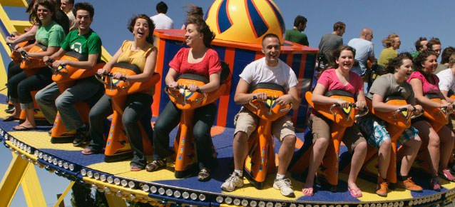 People laughing and riding the Revolution 360 ride as it spins in the air.