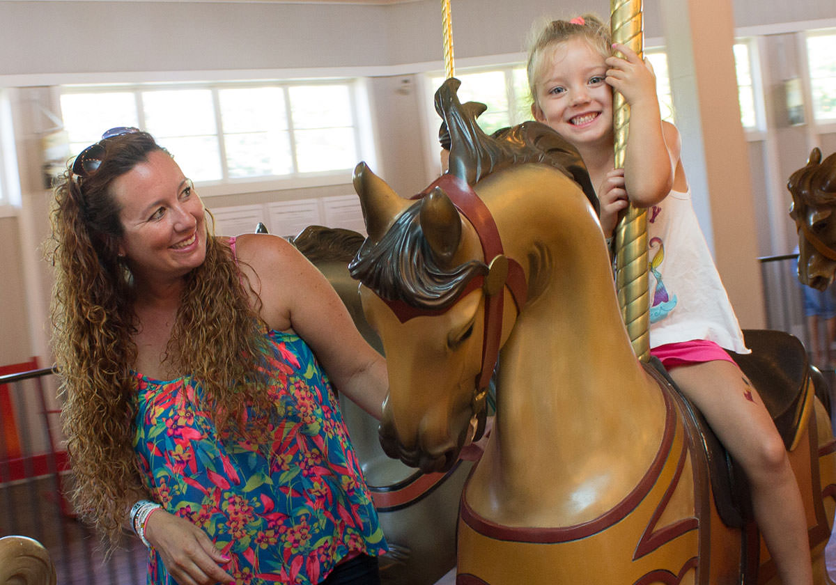 Mom and daughter smiling as they ride the Carousel.