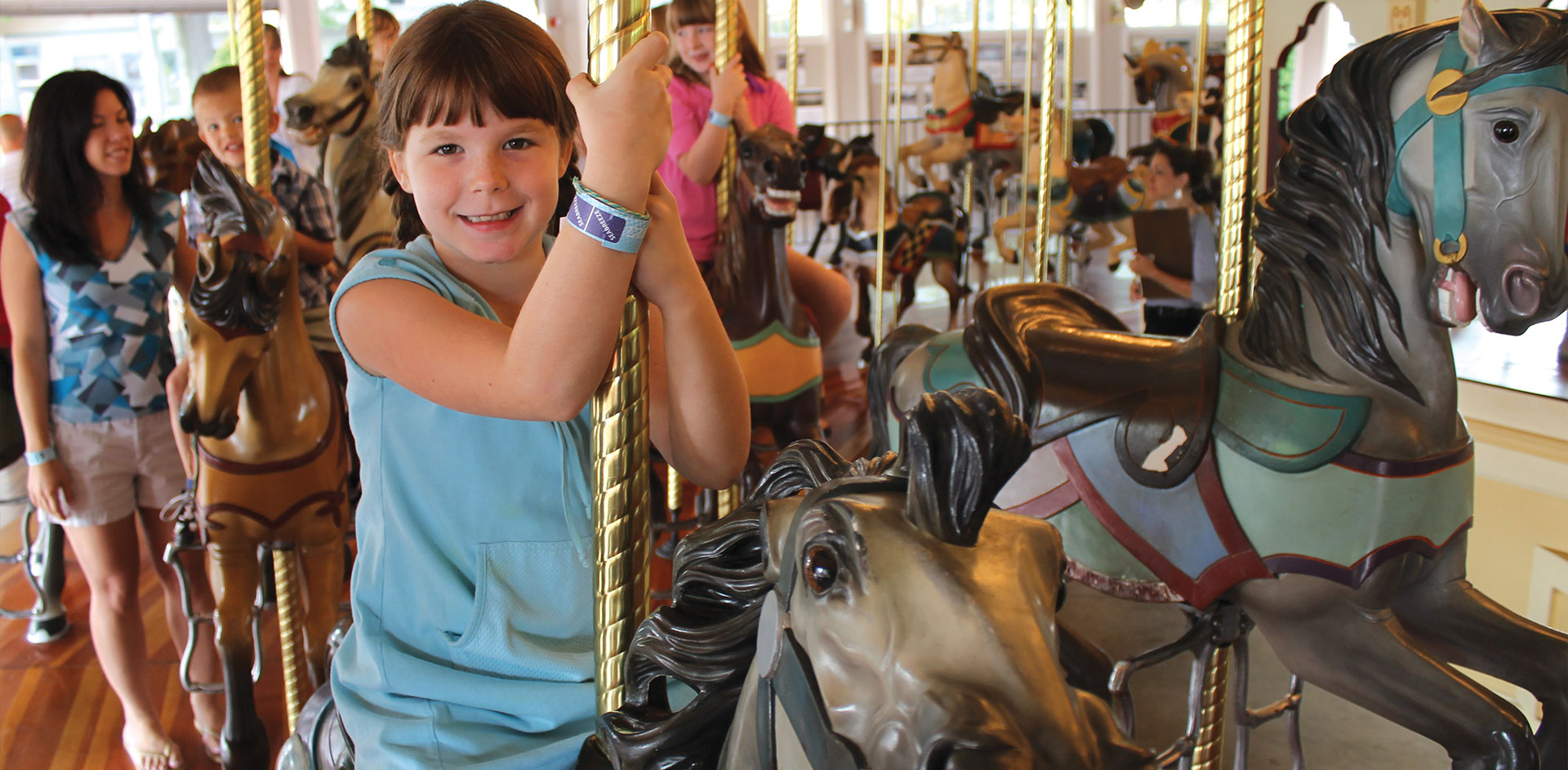 Girl riding carousel ride.