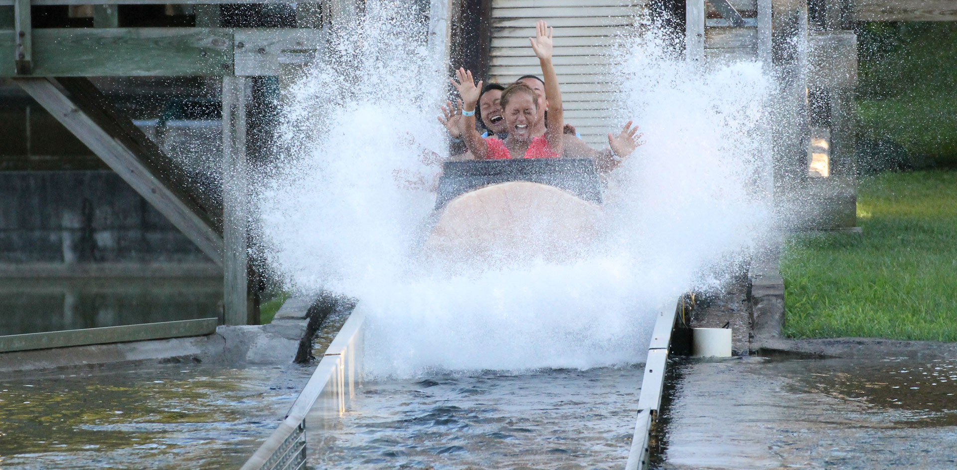 People emerge from Log Flume ride and get soaked with water.