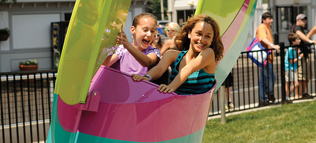 Two girls laughing and smiling while riding the Flyers ride that glides them in the air.
