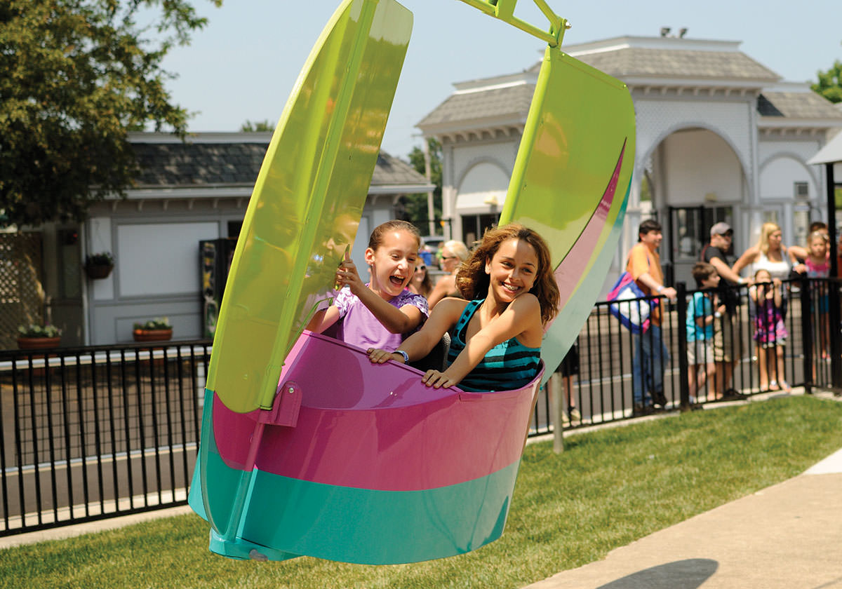 Two girls laugh and smile while riding the Flyers amusement park ride.
