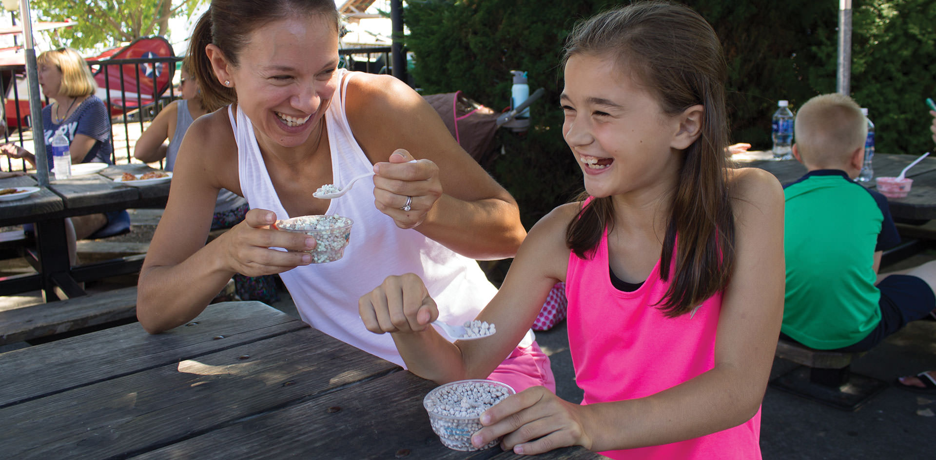 Mom and daughter eating frozen dot ice cream at a picnic table.