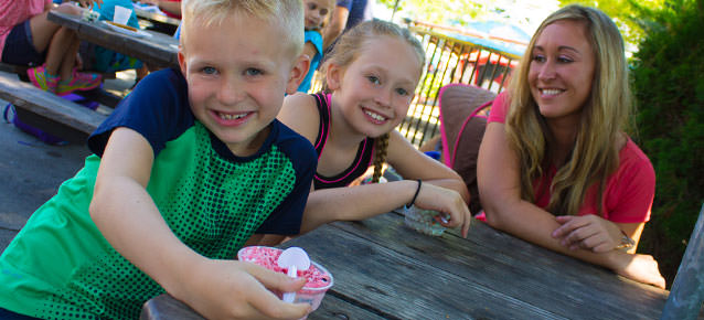 Children eating frozen dot ice cream and smiling at a picnic table.