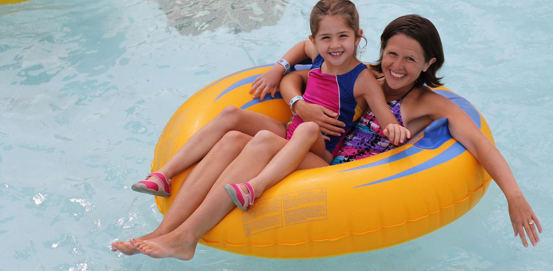 Mom and daughter floating in inner tube.