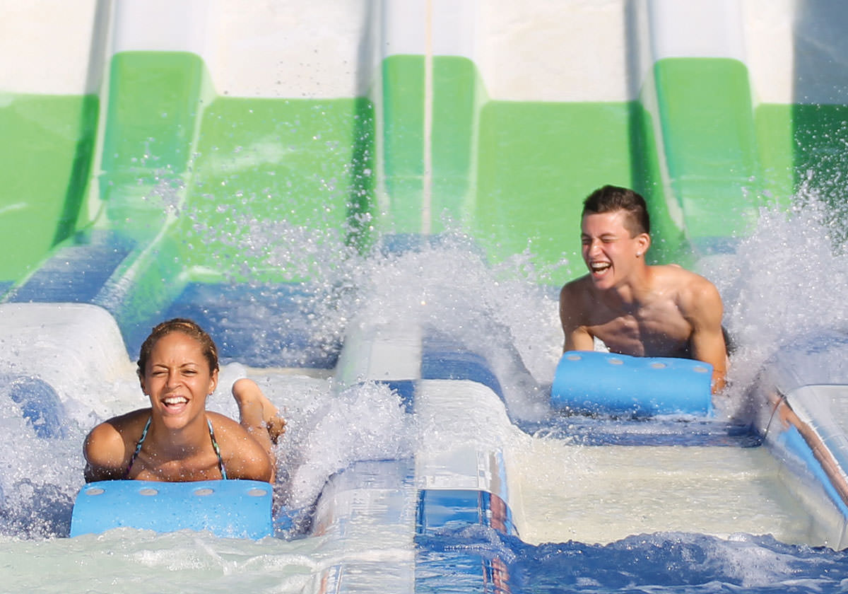 Riders get splashed with water coming down the Hydro Racer water slide ride.