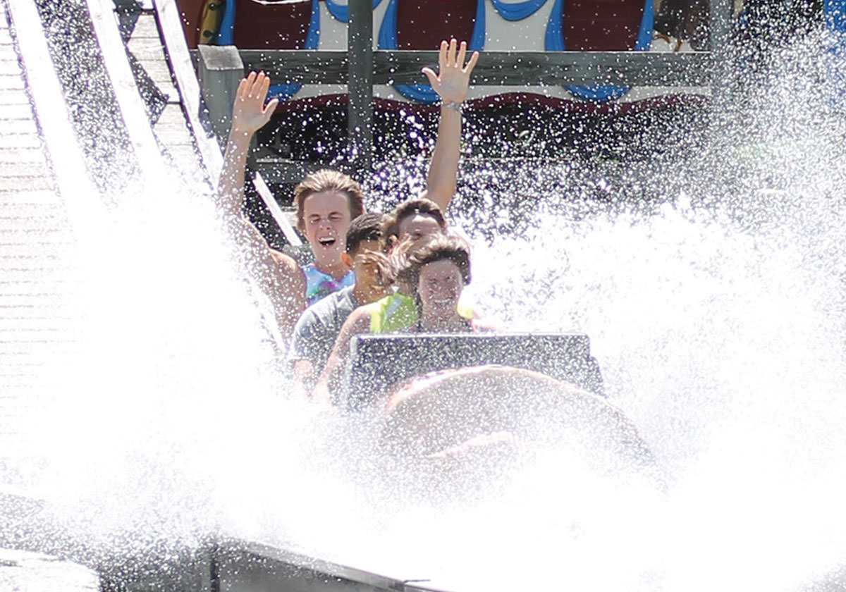 Riders on the Log Flume ride get soaked with water on their way back down.
