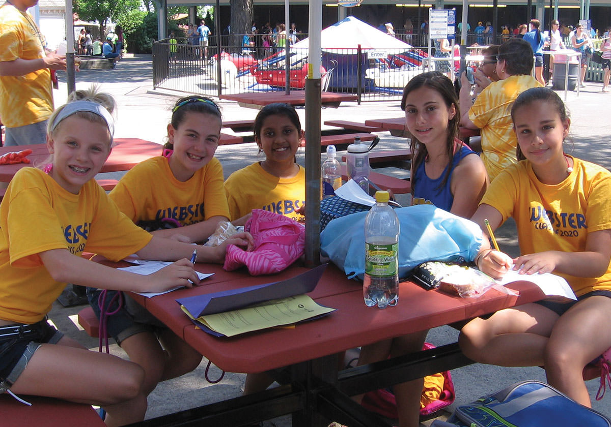 Students smiling and working on schoolwork at picnic table during a school outing.