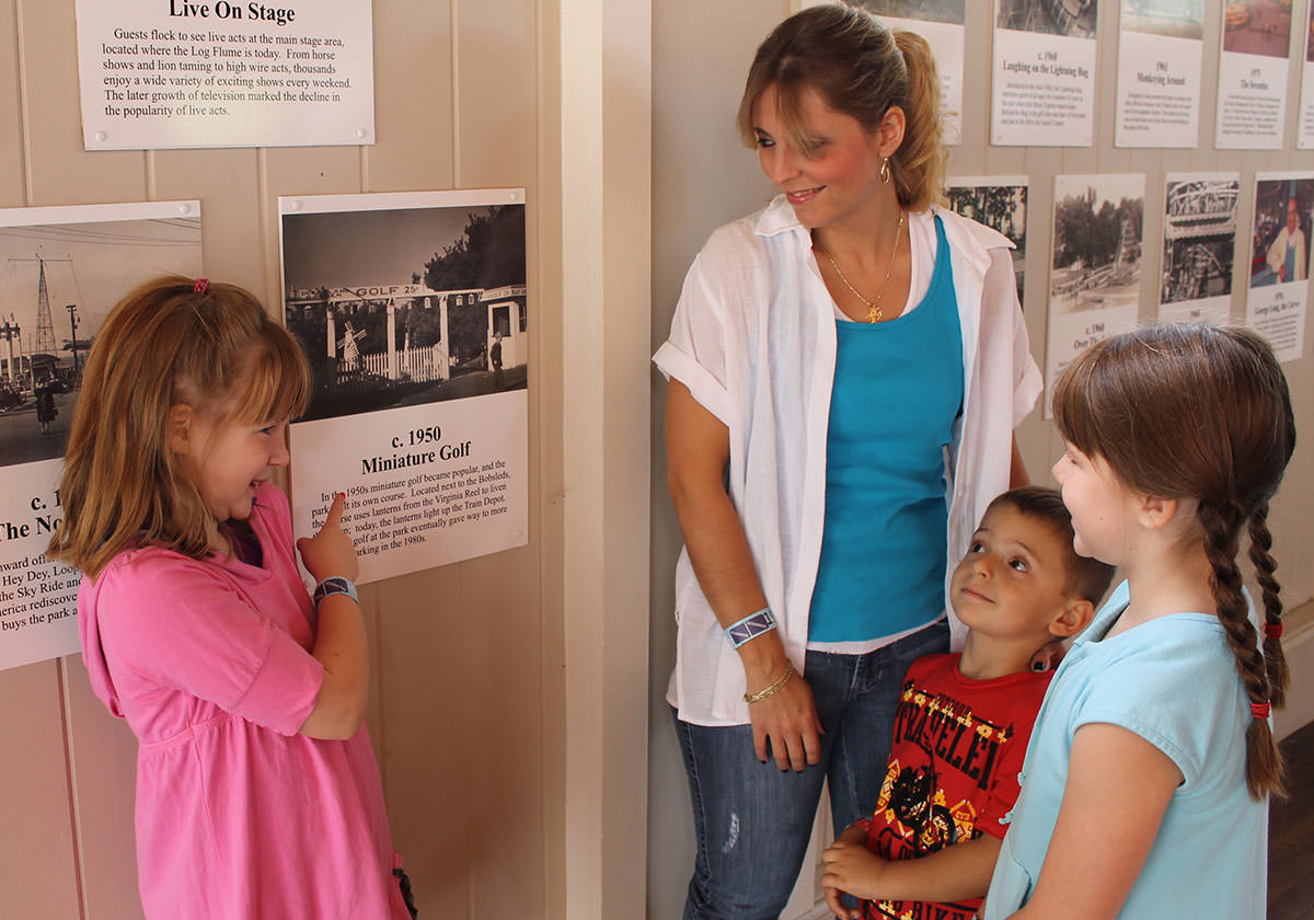 Children and mother look at plaques in the Seabreeze Museum.