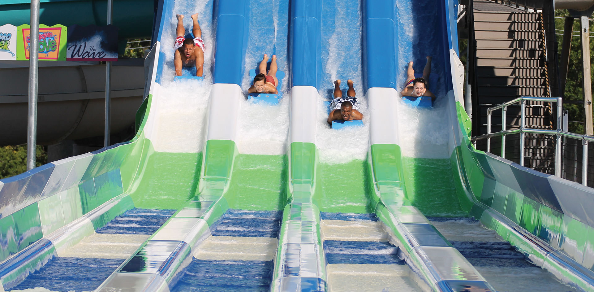 Four adults racing down water slides