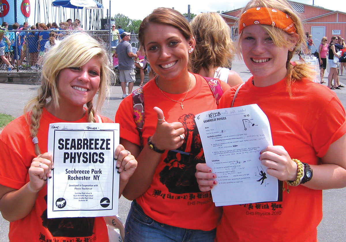 Three female students smiling and showing their completed schoolwork at a school outing at seabreeze.