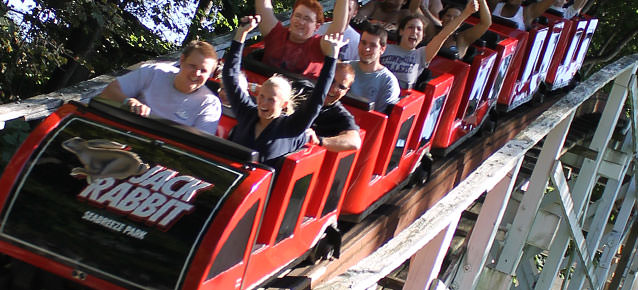 People ride the Jack Rabbit roller coaster ride with their hands up in the air.