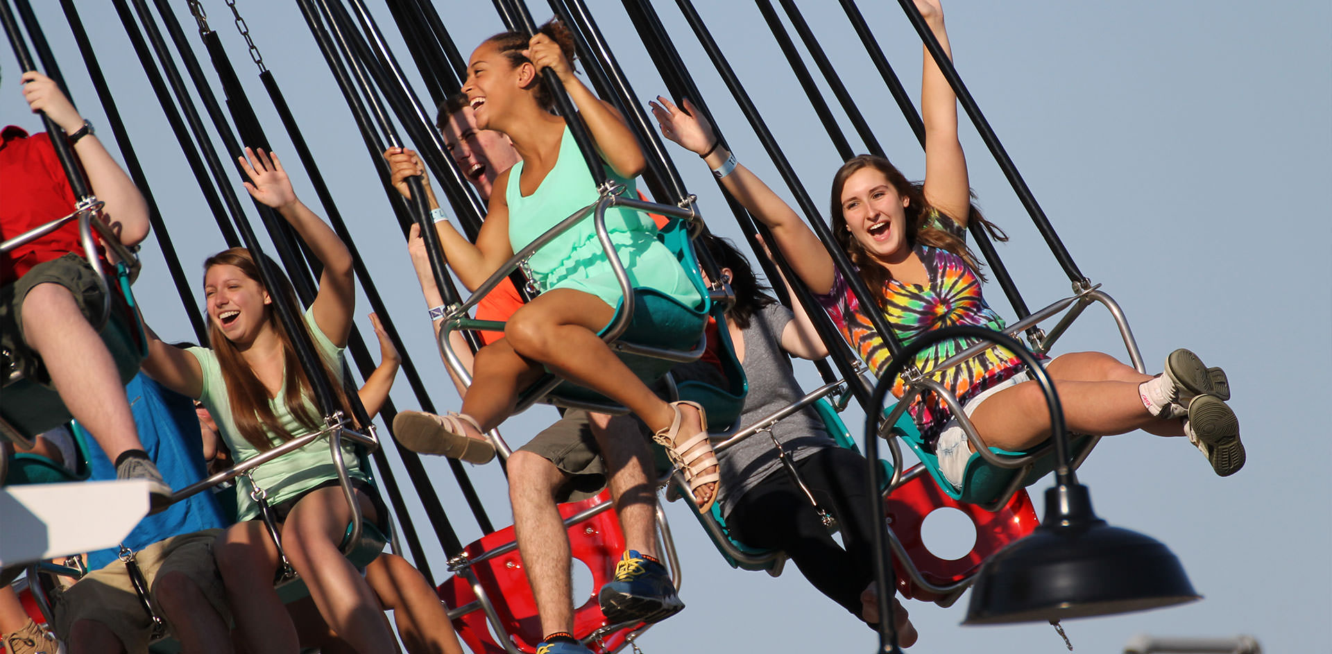 People ride in the air of the flying swing ride at the amusement park.