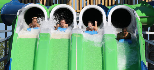 Four people emerging from water slide innertube ride then go down open half of the waterslide ride.
