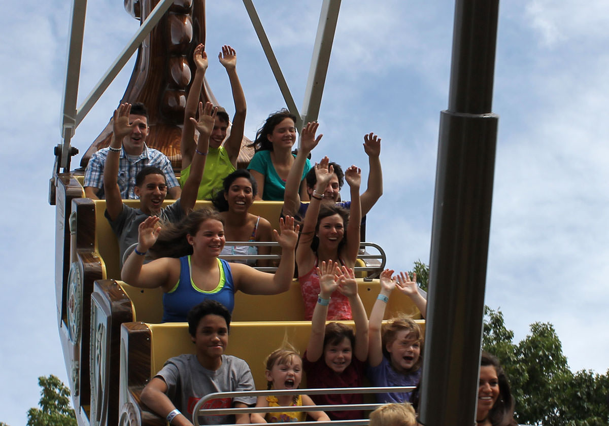 Riders smiling and waving in the air on the Sea Dragon ride.