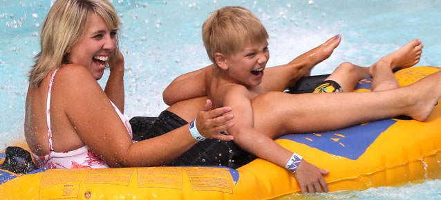 Girl and child splashing and laughing in an inner tube in the water park.