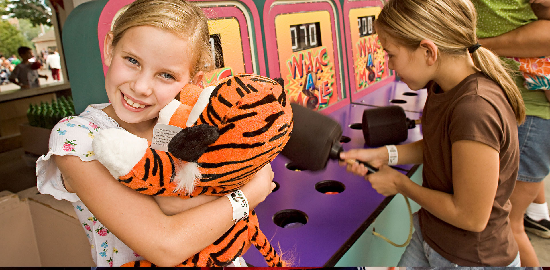 Girl hugging tiger stuffed animal and smiling while other girl plays whack-a-mole at Midway Games.