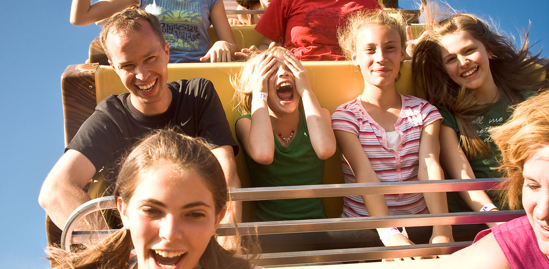 People laughing and riding on a roller coaster at Seabreeze.