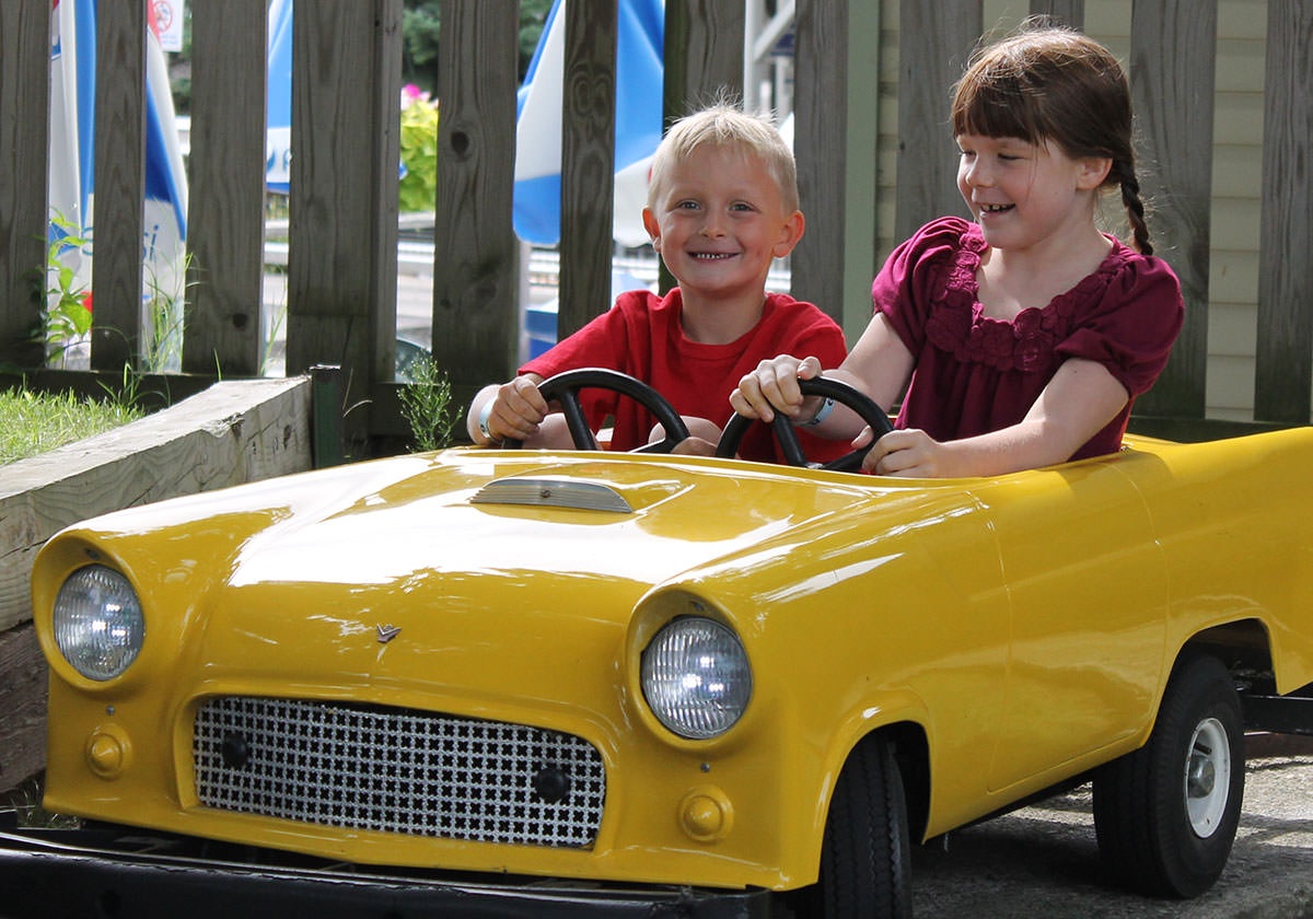 Children riding together in a yellow car at a kiddie ride where cars ride on a track.