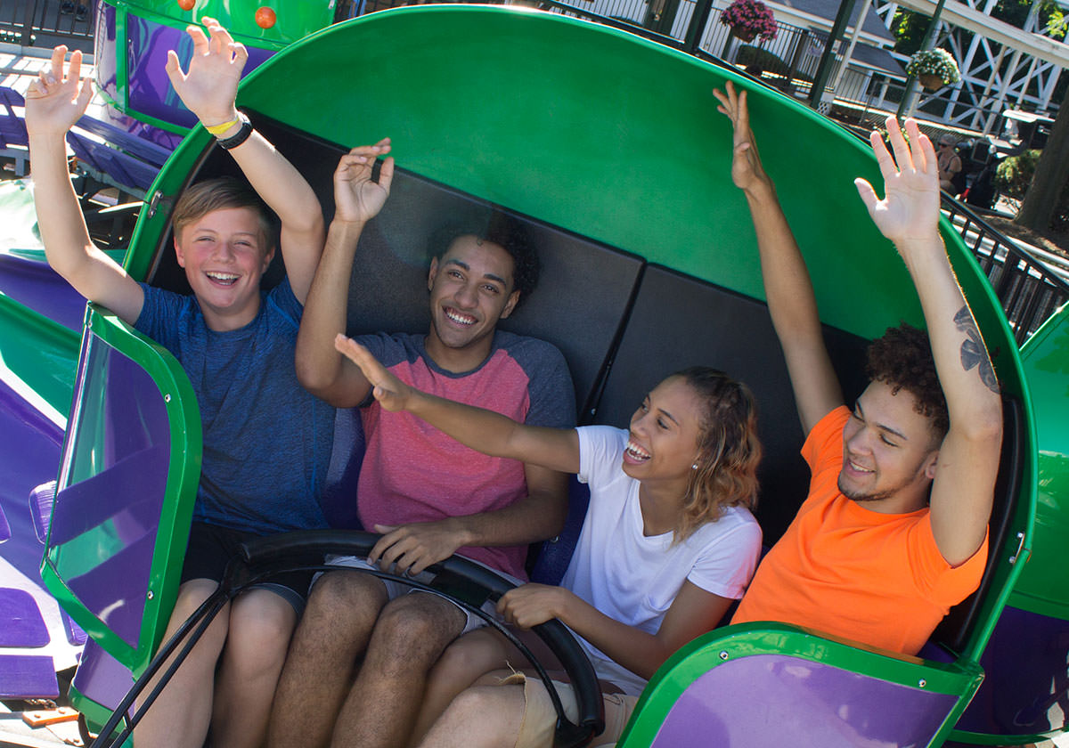 People smiling, laughing, and waving hands on the Tilt-A-Whirl.