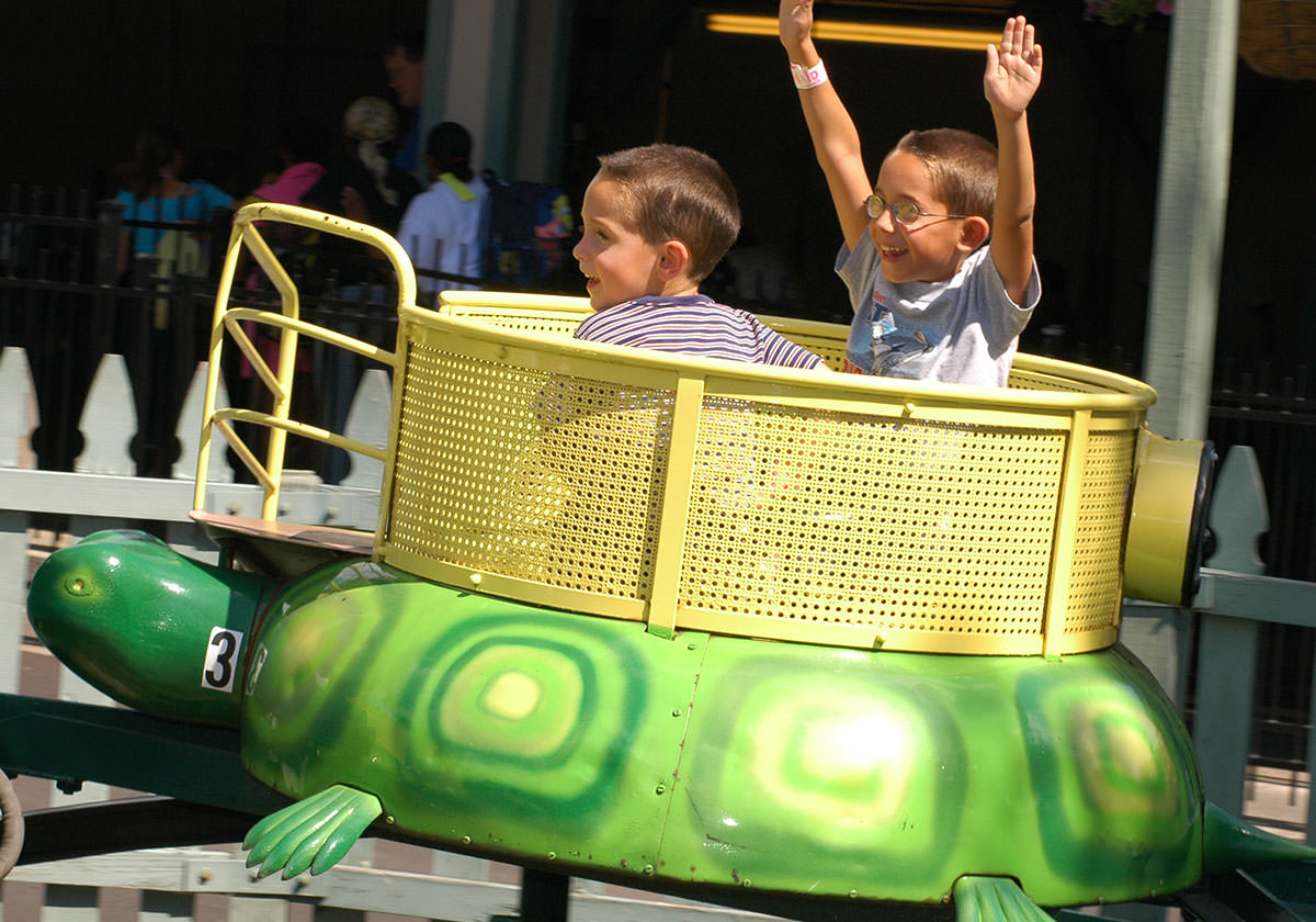 Children smiling as they ride the turtles themed mini rollercoaster at Seabreeze.