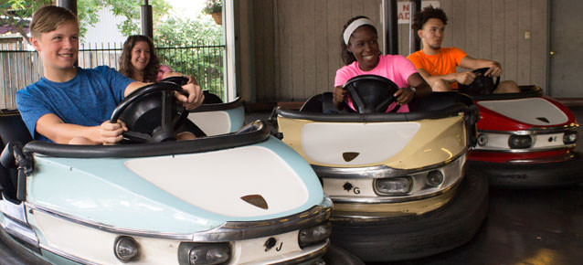 People riding and smiling on the Bumper Cars ride.
