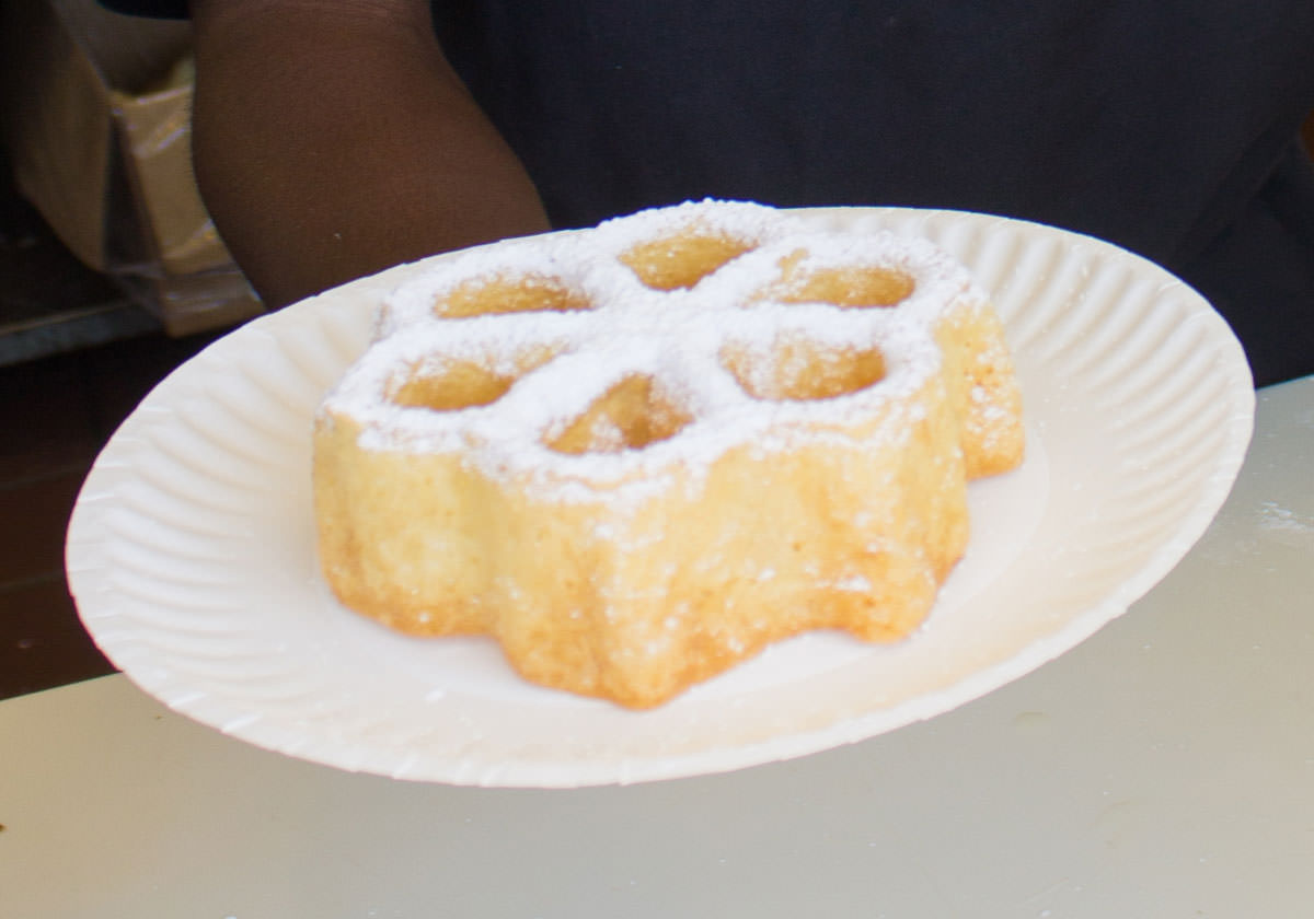 Funnel Cake with powdered sugar on a plate.