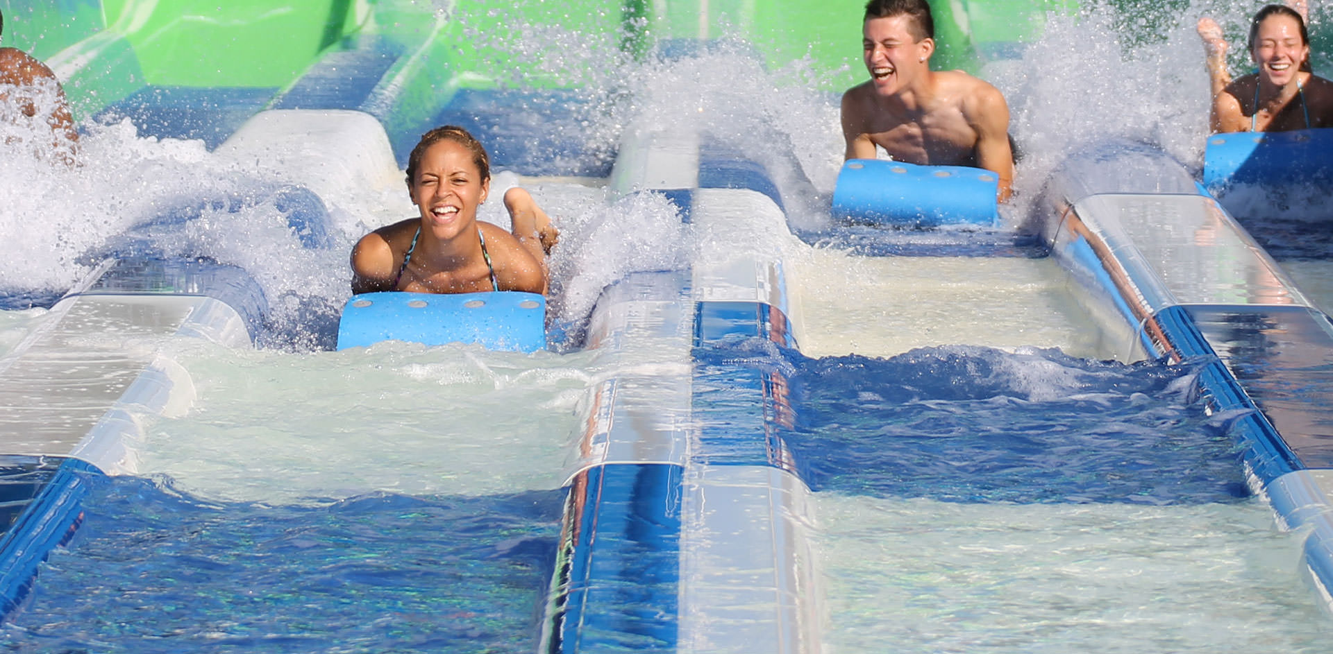 Multiple people going down waterslide ride and getting splashed with water.
