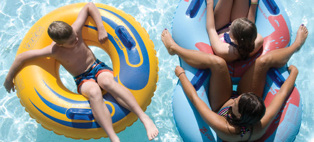 Children riding down the Lazy River water ride in inner tubes.