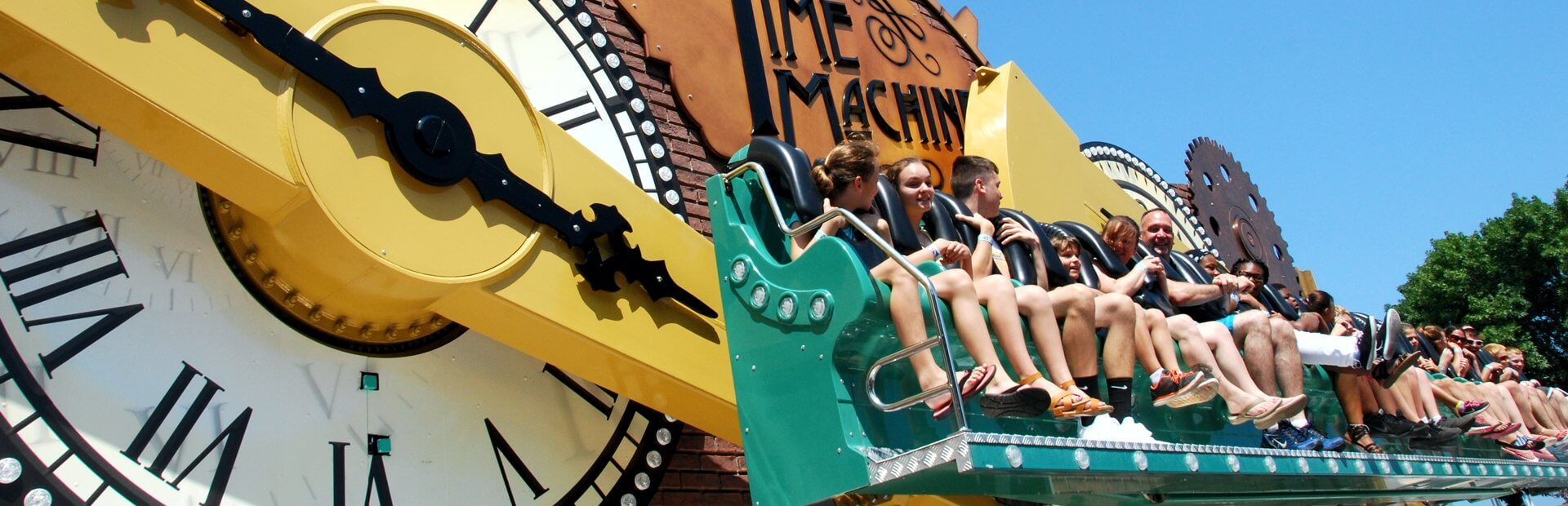 People ride on the giant clock hand of the Time Machine ride.