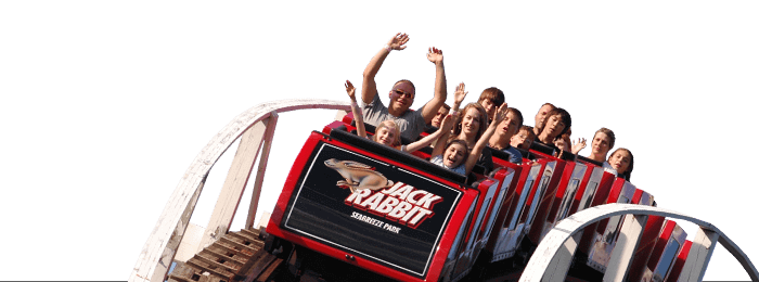 People riding the Jack Rabbit roller coaster ride with hands in the air.