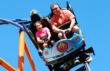 Father and daughter riding the Whirlwind coaster.