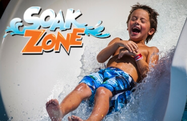 Boy sliding in the Soak Zone water attraction.