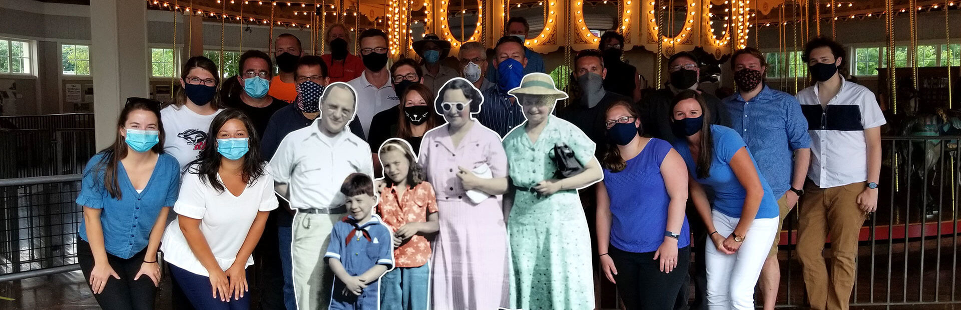 Park staff posing with family cutout.